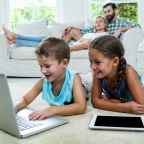 children-using-laptop-front-parents-home_107420-31860