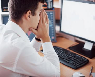 stressful-day-office-young-businessman-holding-hands-his-face-while-sitting-desk-creative-office-stock-exchange-trading-forex-finance-graphic-concept_146671-15021