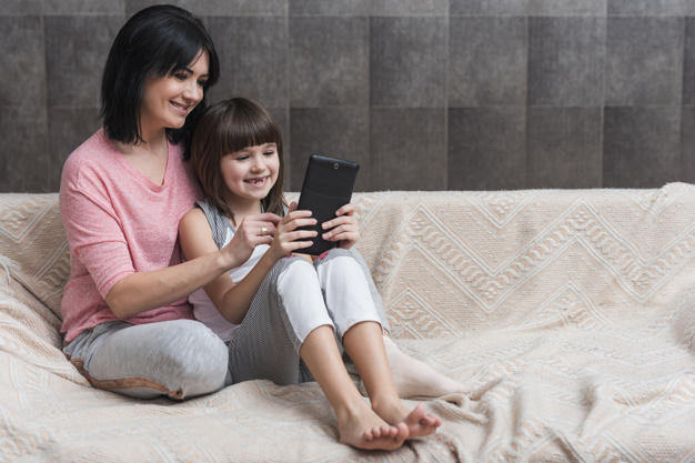 mother-little-daughter-using-tablet-couch_23-2148070440