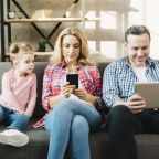 daughter-looking-parents-using-digital-tablet-mobile-phone-home_23-2148045493