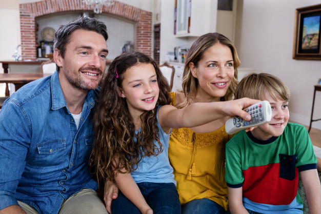 family-watching-television-living-room_107420-25214