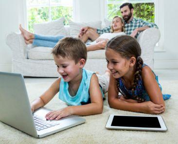 children-using-laptop-front-parents-home_107420-31860